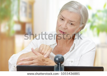 Senior woman in front of a computer monitor with an attached camera showing her doctor a mole on her hand during video call, telemedicine concept