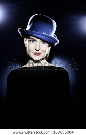 Senior woman in hat studio portrait. Pretty mature lady 60 years old with wrinkled face