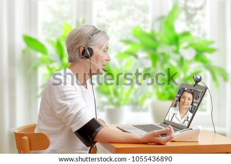 Senior woman in her living room in front of a laptop checking her blood pressure during a video call with her doctor of cardiology