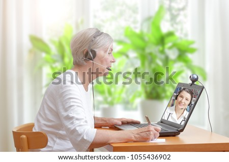 Senior woman in her living room in front of a laptop making notes during a video call with her female doctor