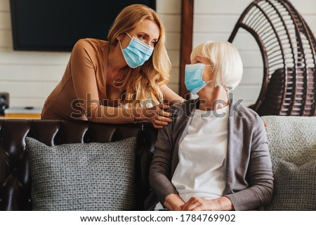 Senior woman in medical mask with social worker visiting her at home Photo stock ©