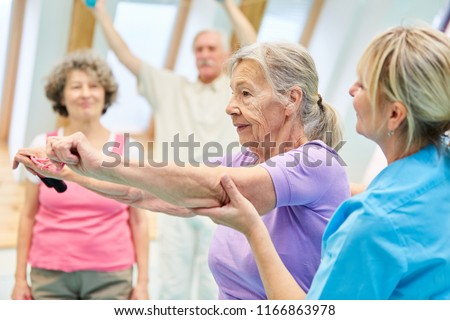 Senior woman in physiotherapy is doing exercise with elastic band with the help of trainer