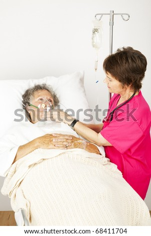 Senior woman in the hospital with lung disease, getting oxygen from a nurse.