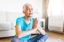 Senior woman in the prayer position . Woman practicing yoga, relaxing in prayer position on mat, Padmasana exercise, elderly woman wearing sportswear working out, meditating in yoga studio or at home