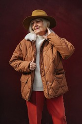 Senior woman in trendy outerwear and hat looking away while standing against vinous wall. Aged female in stylish outerwear