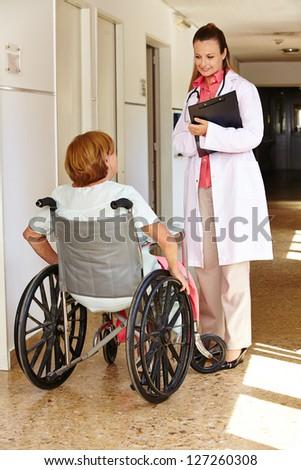 Senior woman in wheelchair talking to nurse in a hospital