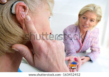 Senior Woman Inserting A Hearing Aid In Her Hear. Focus On The Colored Hearing Aid In Specialist\'S Hand