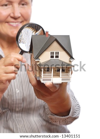 Senior woman inspecting a home with a magnifying glass - stock photo