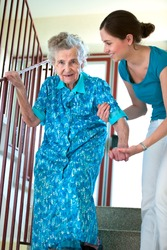 Senior woman is climbing stairs with caregiver