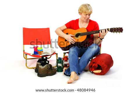 Senior woman is playing guitar at the campground