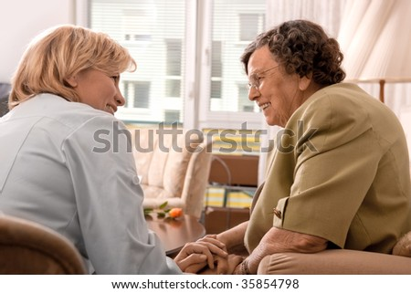 Senior woman is visited home by her doctor or caregiver at home