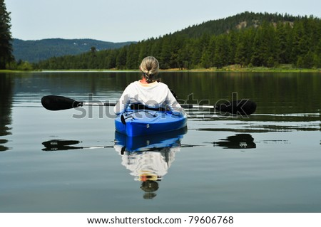 Senior woman kayaking on lake