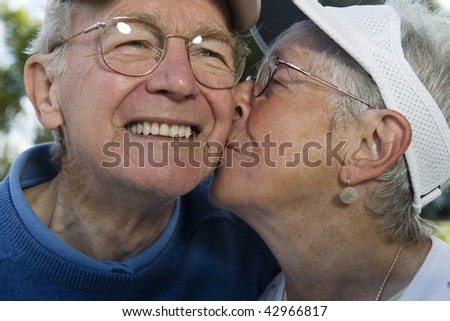 Senior woman kissing senior man on the cheek. Horizontally framed shot.