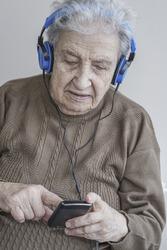 senior woman listening music with headphones and smart phone
