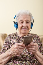 senior woman listening music (with smartphone / ipod)