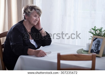Senior woman looking at dead husband\'s picture