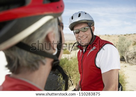 Senior woman looking at male bicyclist