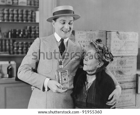Senior woman looking at man holding gin bottle