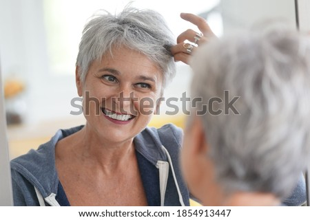 senior woman looking at that white hair in a mirror ストックフォト ©
