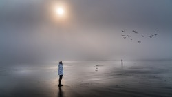 Senior Woman looking out into the Dense Fog over the Pacific Ocean in Cox Bay at the Pacific Rim National Park on Vancouver Island, British Columbia, Canada
