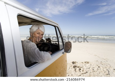 Senior woman looking out of window of camper van on beach, smiling, portrait