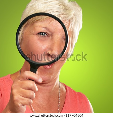 Senior Woman Looking Through A Magnifying Glass On Green Background