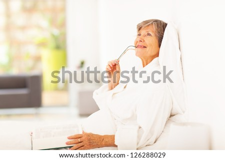 senior woman lying on bed daydreaming