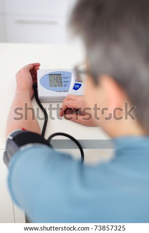 senior woman measured her blood pressure - stock photo