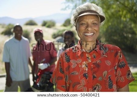 Senior woman on golf course, (portrait), family in background