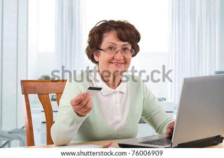 senior woman online shopping on laptop at home