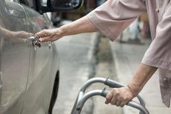 senior woman open car door with walker on street.