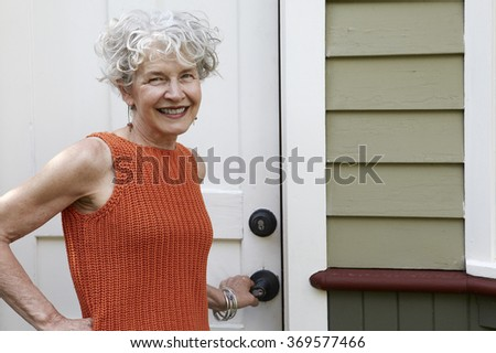 Senior woman opening the door of her home
