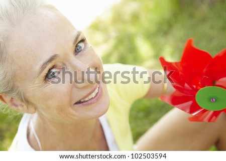 Senior woman outdoors with toy windmill