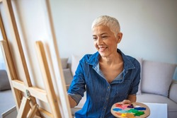 Senior woman painting at home. Happy elderly woman looking at her painting at home. Happy retired woman painting on canvas for fun at home. Portrait Of Senior Female Artist Working On Painting