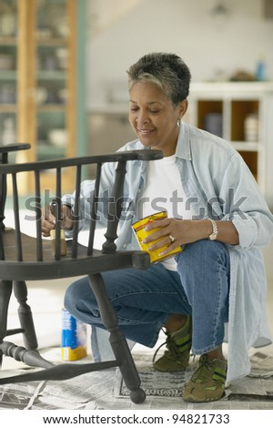 Senior woman painting chair