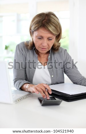 Senior woman pensioner calculating bills