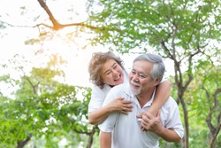 Senior woman piggy back senior man with love and happiness in park. Elderly asian couple have good health, smiley faces. Old couple always stay together. Grandmother, grandfather have long life