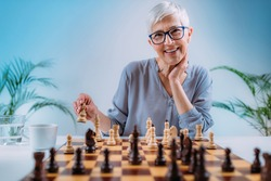 Senior woman playing chess. Cognitive rehabilitation activity.