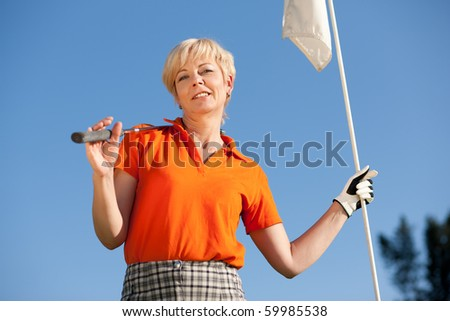 Senior woman playing golf holding the flag in her hand