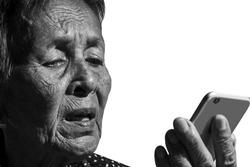 Senior woman playing  smartphone