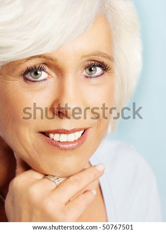 Senior woman portrait,closeup, on  cyan background with white hair and hand on chin