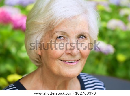 Senior woman portrait, outdoors, in front of the garden, smiling to camera