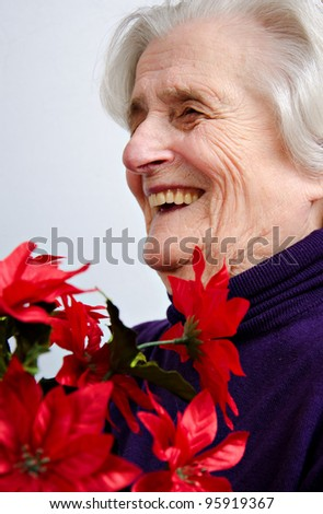 Senior woman portrait, smiling with a bunch of artificial flowers