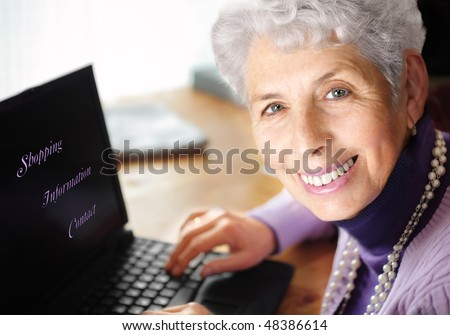 """Senior woman portrait, typing on laptop and smiling great at camera. With text on laptop:""""Shopping, Information,Contact"""""""