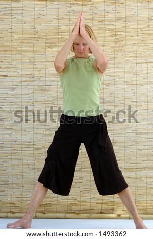 "senior woman practicing vinyasa yoga or ""flow"" yoga"