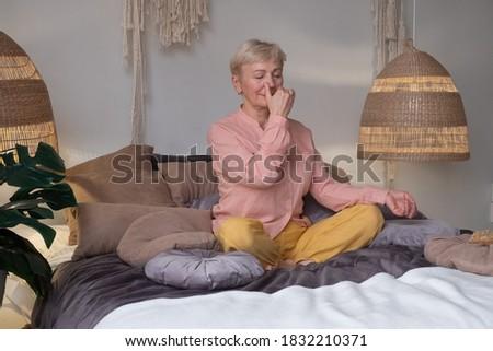 Senior woman practicing yoga at home, making Alternate Nostril Breathing exercise, nadi shodhana pranayama pose, working out Stock foto ©