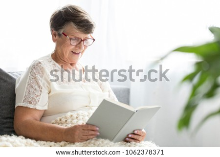 Senior woman reading a book alone in a retirement home