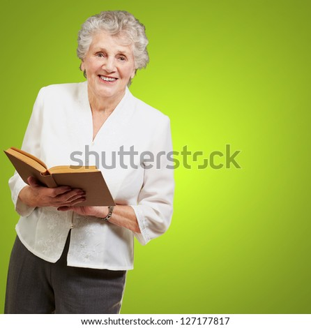 Senior woman reading a book isolated on green background