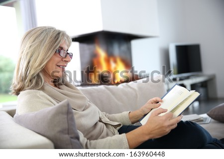 Senior woman reading book at home by fireplace