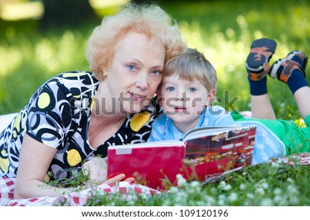 Senior woman reading book to her grandson in the park